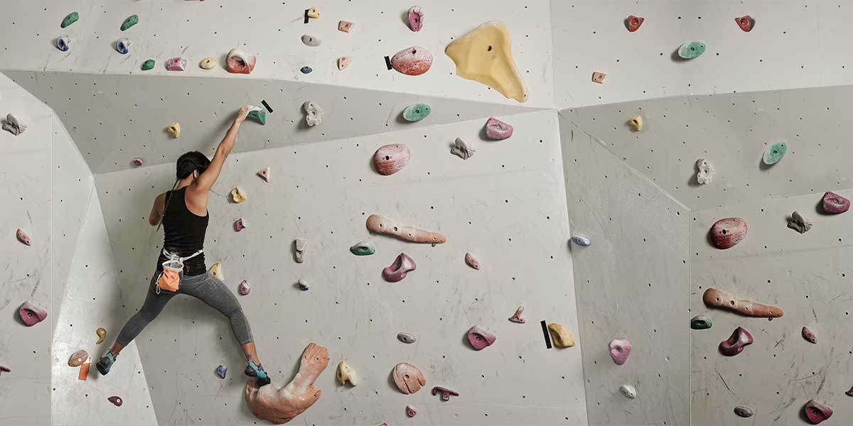 Image of woman climbing a rock wall